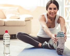 ფეხების სიმძიმის პროფილაქტიკისთვის ქალი ასრულებს იოგას ვენურ ვარჯიშებს